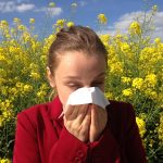 allergies and woman blowing nose