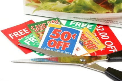 pile of money saving coupons with scissors