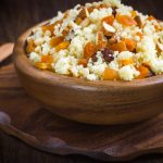 wooden bowl with Couscous with dried fruits and nuts