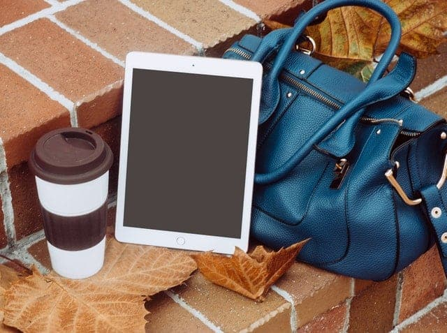 blue bag on steps with tablet and coffee cup
