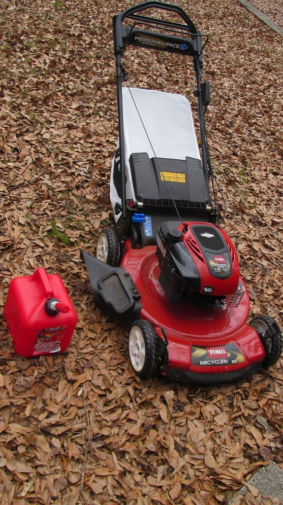 lawnmower and gas can on a carpet of fallen leaves