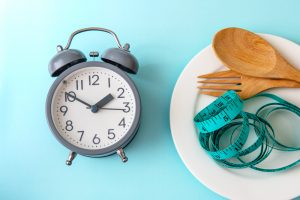 clock next to plate with tape measure and spoon