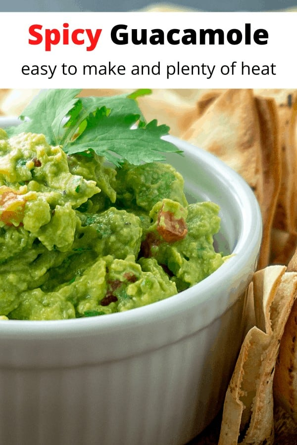 fresh guacamole in a white bowl with tortilla chips