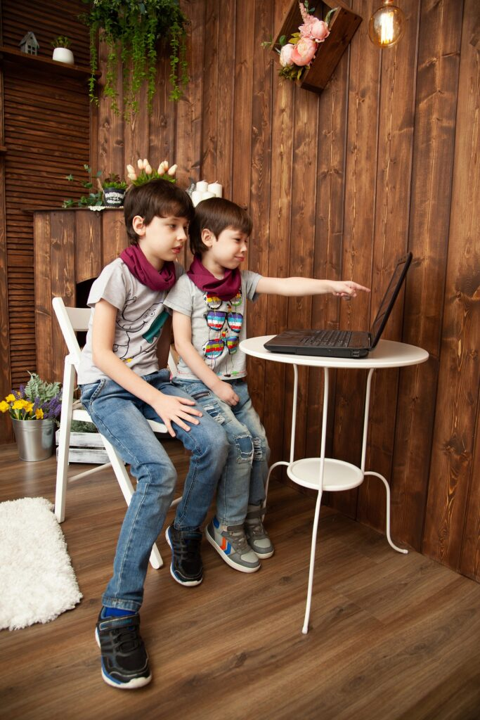 two kids watching the screen of a computer
