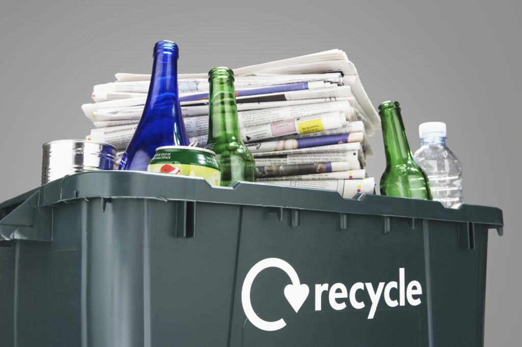 newspaper and bottles in recycling can