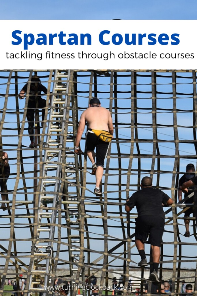 people climbing obstacle course with text Spartan Courses tackling fitness through obstacle courses