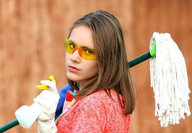 woman with safety glasses on holding mop and cleaning supplies