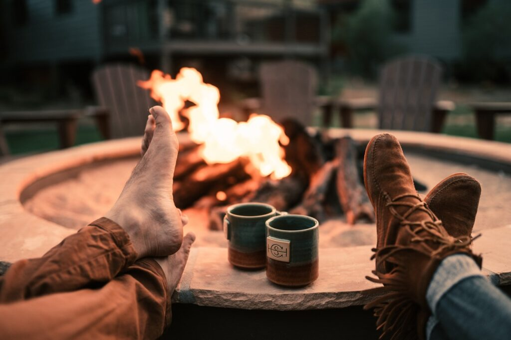 fire in fire pit with feet on edge and coffee mugs