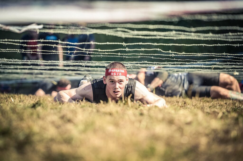 man on ground during spartan race