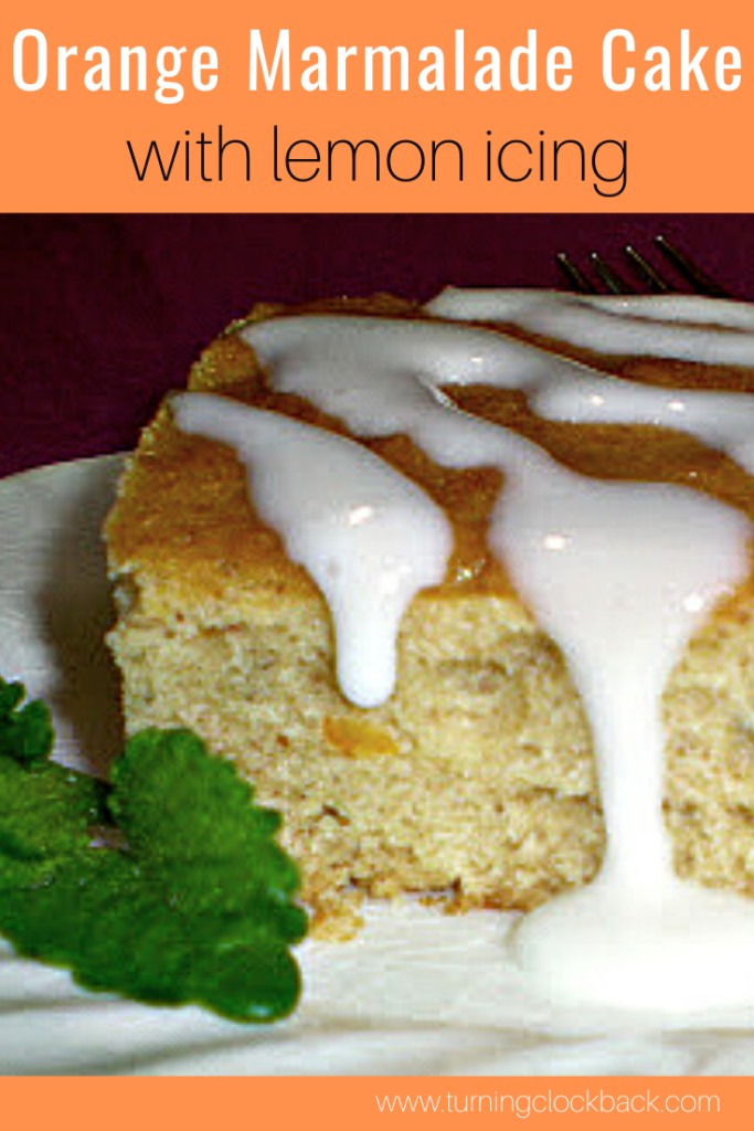 Orange Marmalade Cake with lemon icing on a white plate with fresh mint