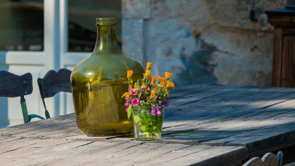 outdoor table on backyard patio with glass bottle and flowers