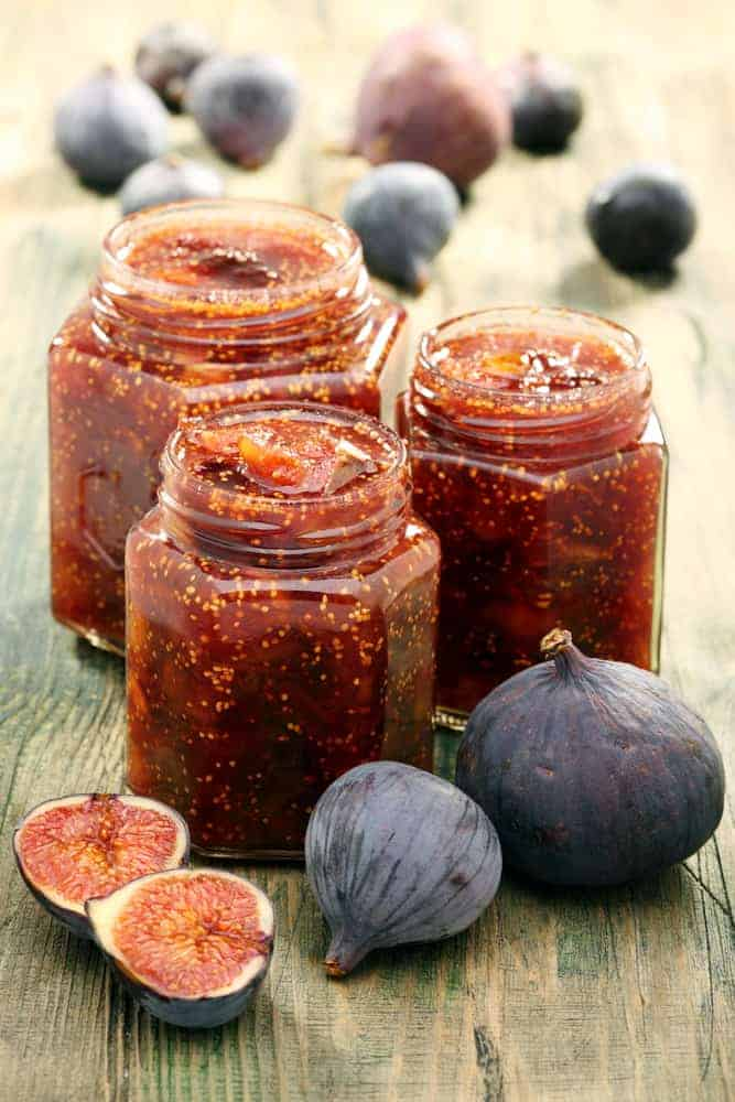 Figs and jam in glass jars on a wooden table.