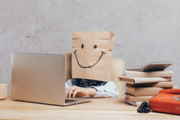 child with brown paper bag on head sitting at laptop