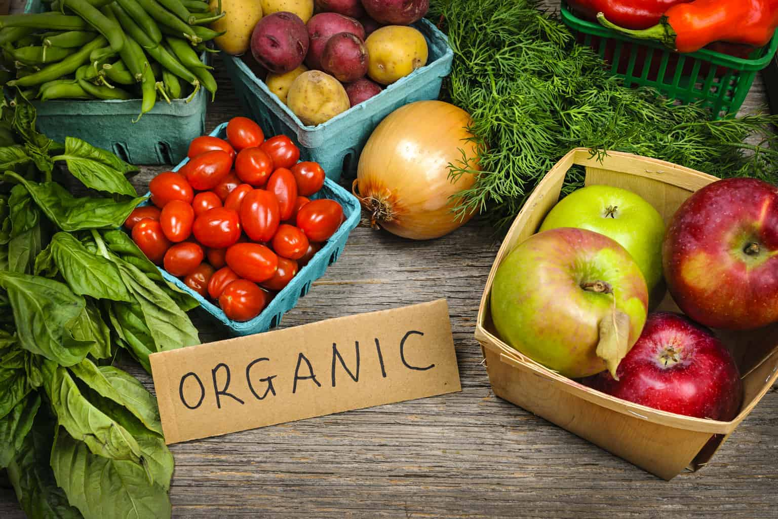 pile of organic produce and text overlay 'How to Start Saving Money on Organic Food'