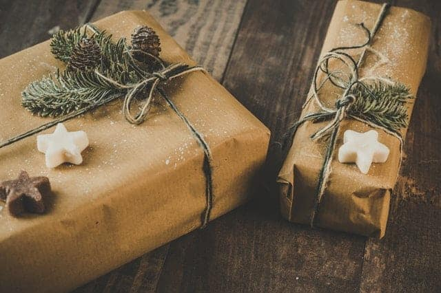 gifts wrapped in brown paper bags with pine branches