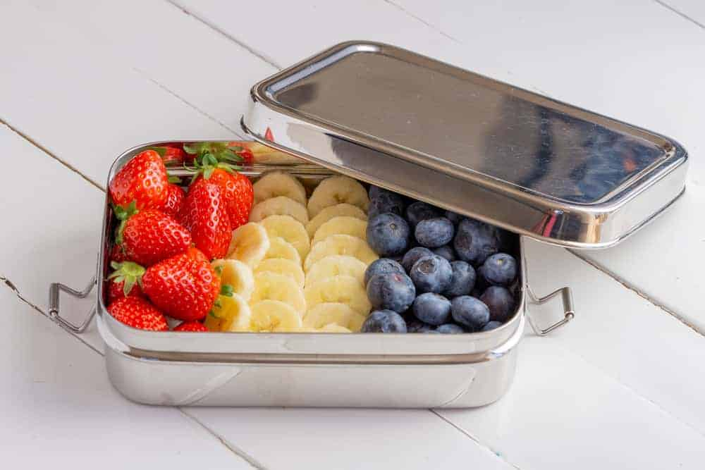 Blueberries, bananas and strawberries in plastic free container.