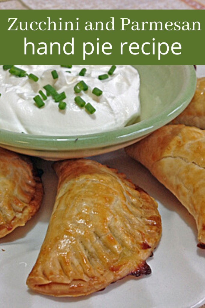Zucchini and Parmesan hand pies on a plate with sour cream dip