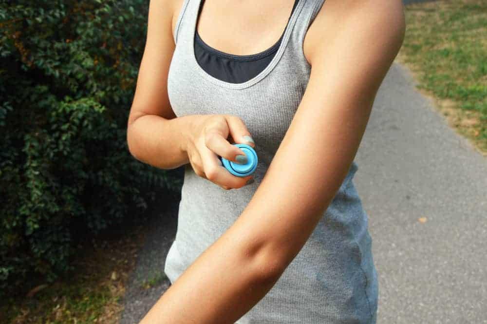 woman spraying herself with bug spray outdoors