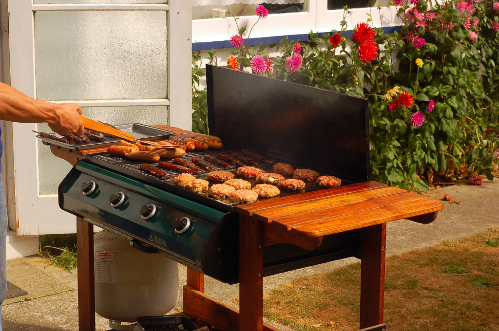 person grilling on outdoor grill on stone patio