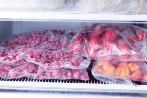 Frozen berries and fruits in bags in freezer, close up. Stocks of meal for the winter.