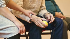 elderly people sitting and doing therapy