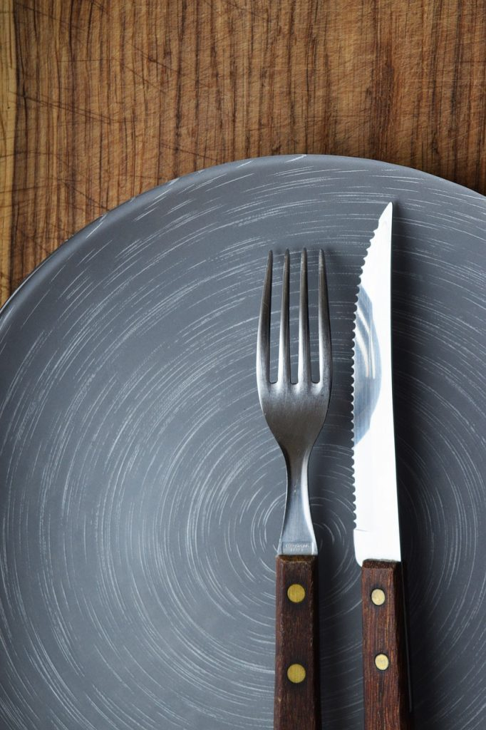 plate knife and fork on wooden table