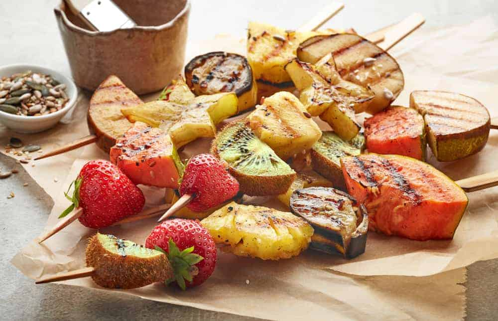 various grilled fruit pieces on wooden skewers