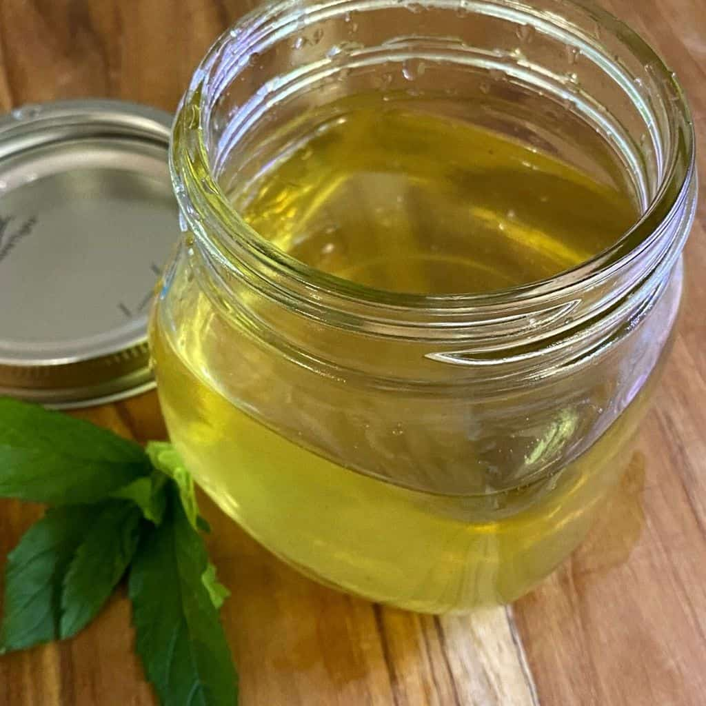 mint syrup in small jar with fresh mint on cutting board