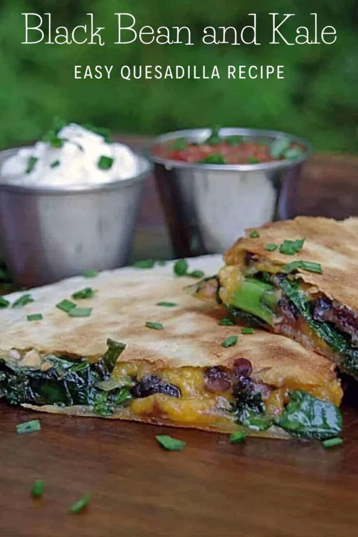 Kale and black bean quesadillas on a plate with containers of sour cream and salsa