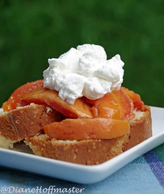 cake topped with fresh peaches and whipped cream