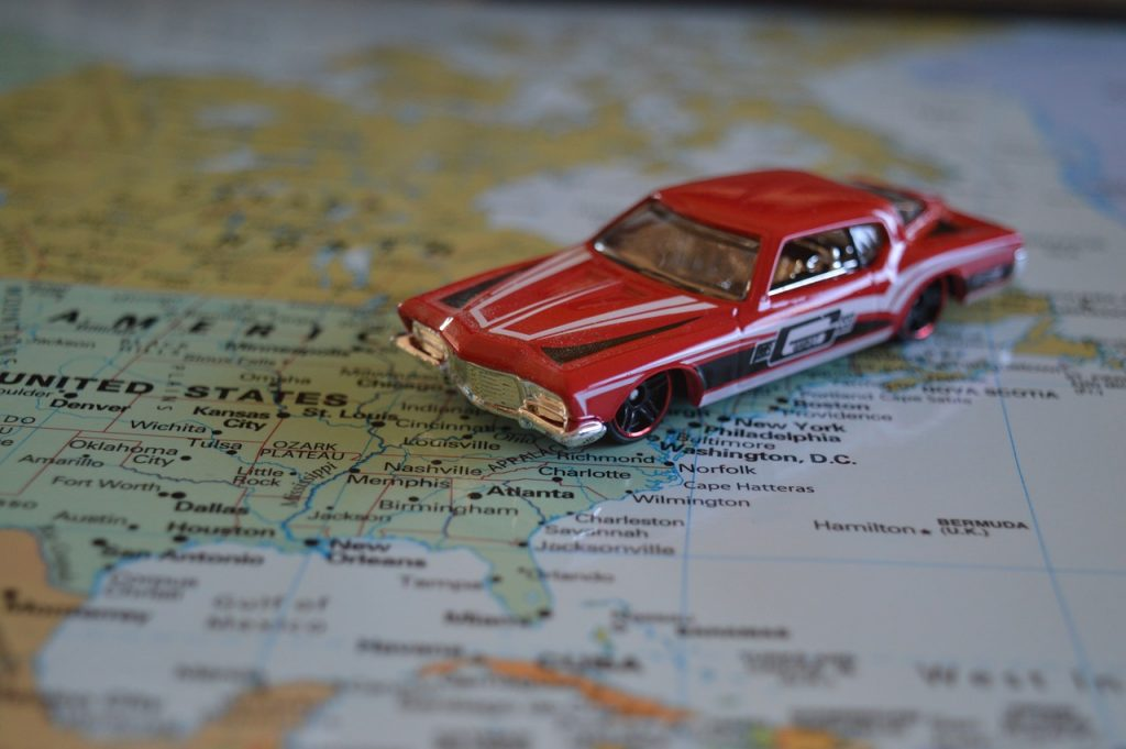 small toy car on map indicating long distance travel