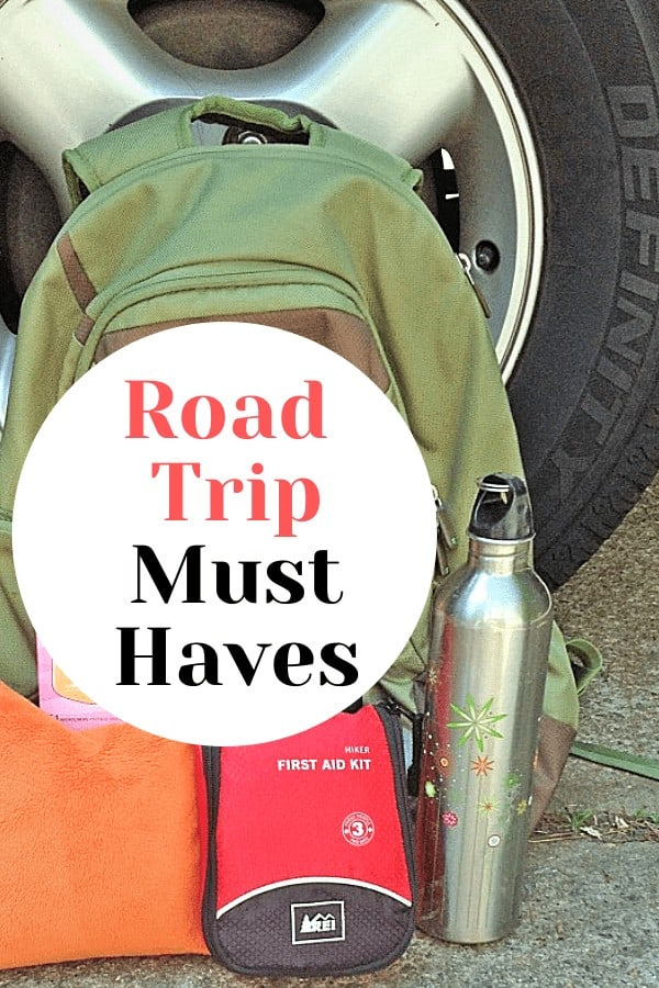 backpack and other road trip essentials in front of a car tire