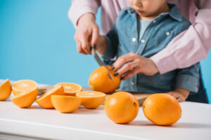 adult and child cutting oranges
