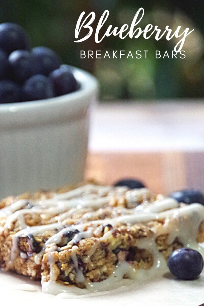 Blueberry Pecan Breakfast Bar on parchment paper with fresh blueberries