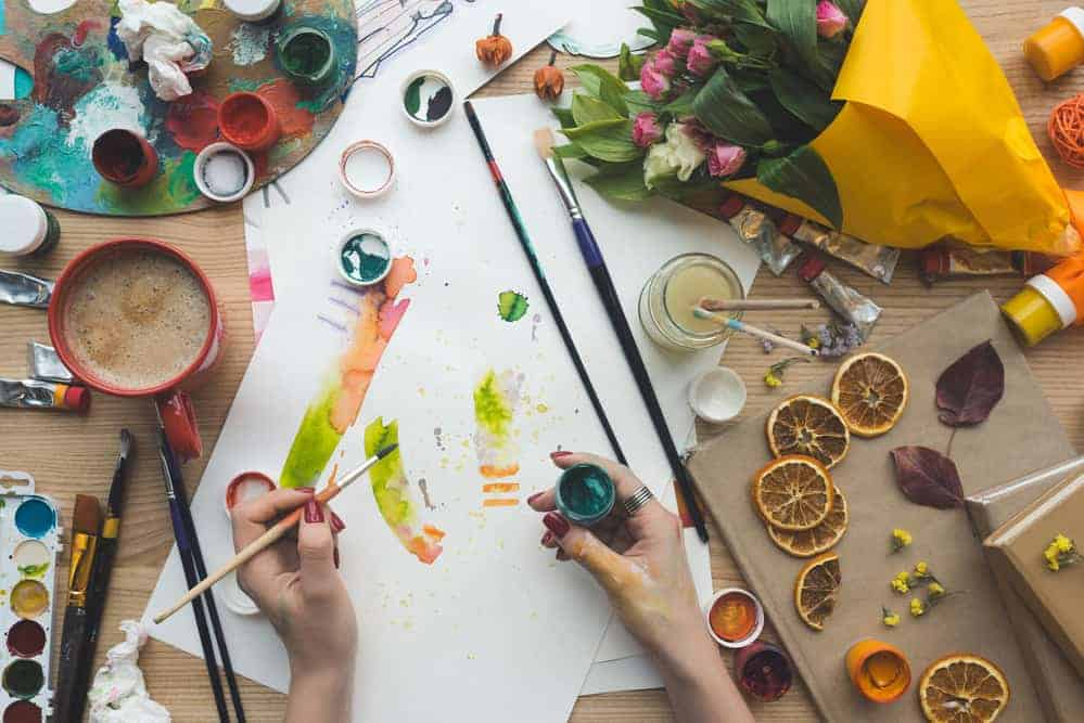 art with paint brushes, small jars, and art supplies