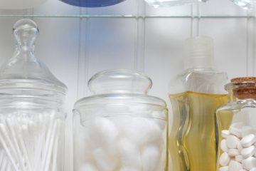 Closeup of two shelves of a medicine cabinet. A bottle of tablets, cotton balls and cotton swabs and assorted jars and bottles of soap and lotions. Square format.