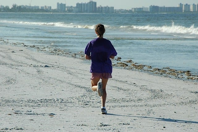 woman jogging on beach in summer