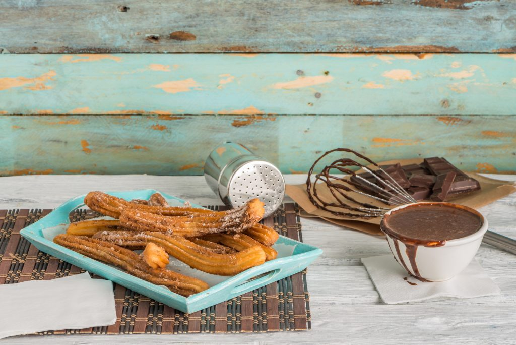 Traditional churros with hot chocolate dipping sauce on wooden counter top.