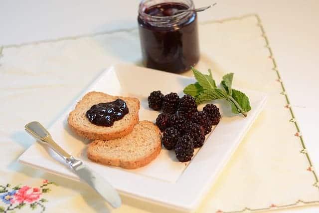 blackberry jam on toast on white plate with fresh blackberries