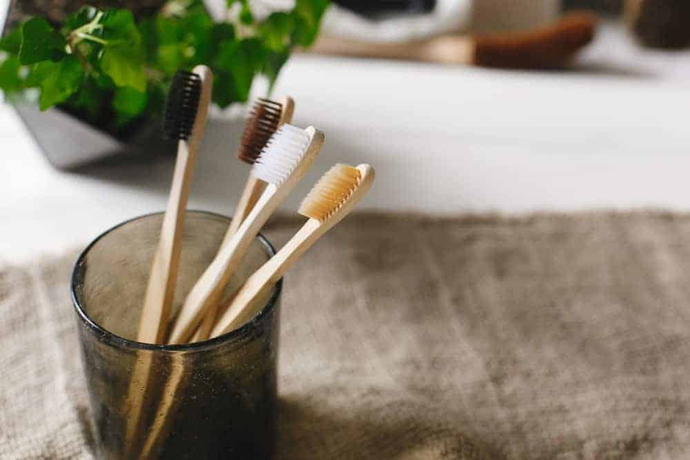 clean eco natural bamboo toothbrushes in glass on rustic background wi