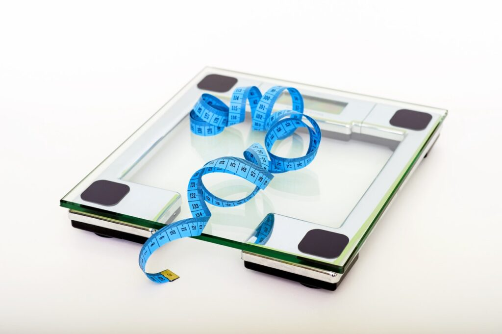 scale and measuring tape indicating weight loss