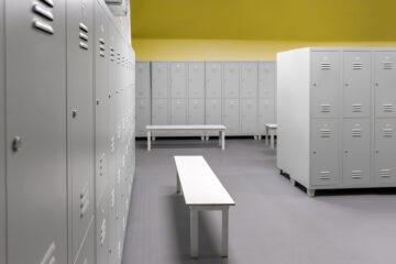 Row of steel lockers along the yellow wall and white benches