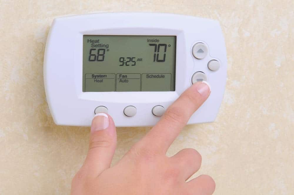 Closeup of a womans hand setting the room temperature on a modern programmable thermostat.