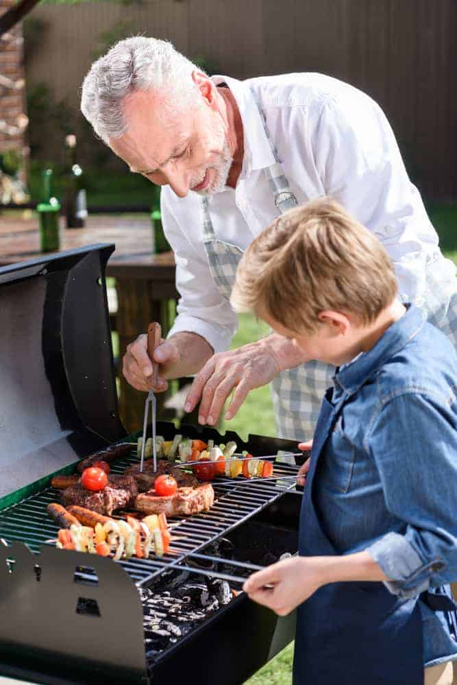 child and adult grilling meat together