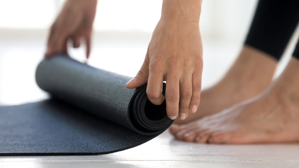 Sporty girl rolling black yoga mat before or after workout
