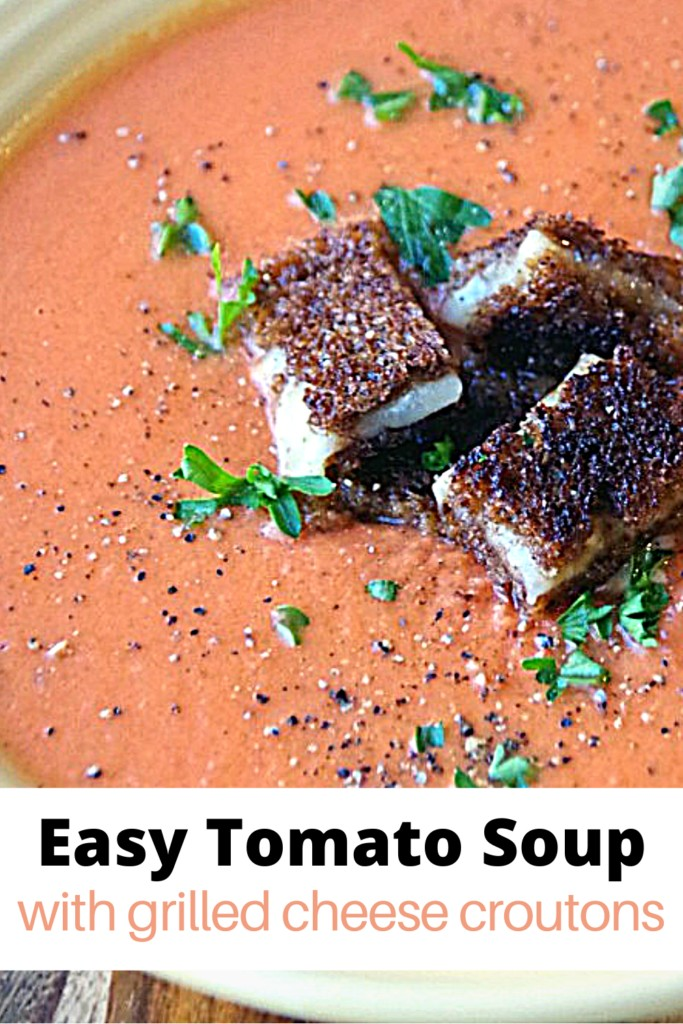 bowl of creamy tomato soup topped with grilled cheese croutons