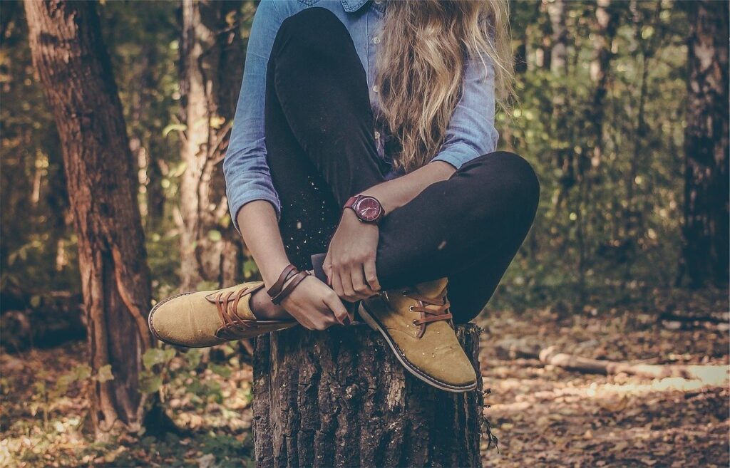 woman sitting on tree stump in rustic clothes
