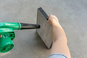 Woman hand holding blower to clean dirty air purifier HEPA filter.