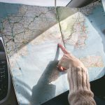 adult in car with map