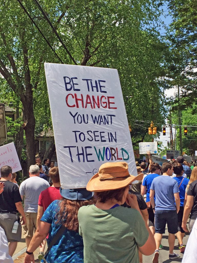 people marching for change and holding a sign